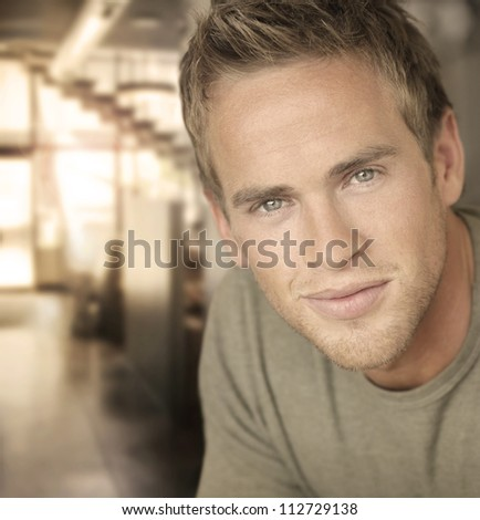 Portrait of an handsome young man in office setting in warm light - stock photo