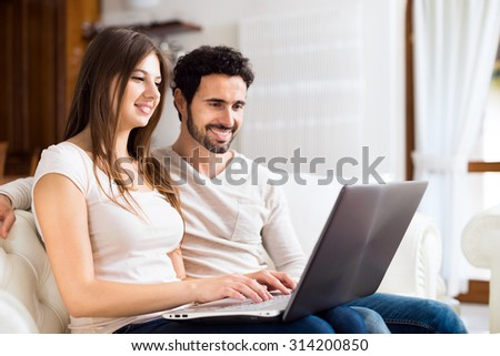Portrait of an happy couple using a laptop computer in their house. Shallow depth of field, focus on the woman - stock photo