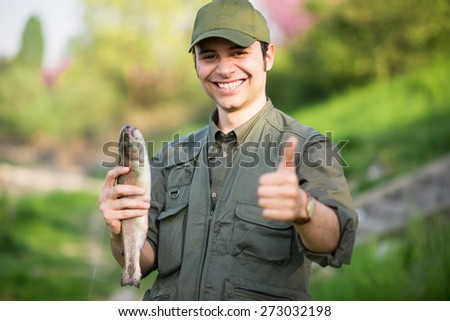 Portrait of an happy fisherman holding a fish - stock photo
