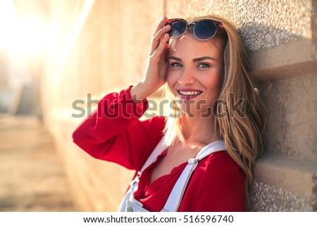 Portrait of an happy girl posing next to a wall in the street