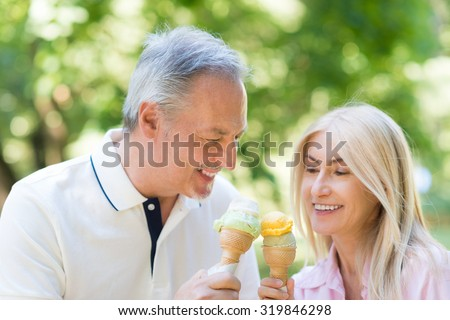 Portrait of an happy mature couple eating an ice cream in a park