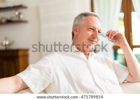 Portrait of an happy mature man relaxing on the couch while holding his eyeglasses