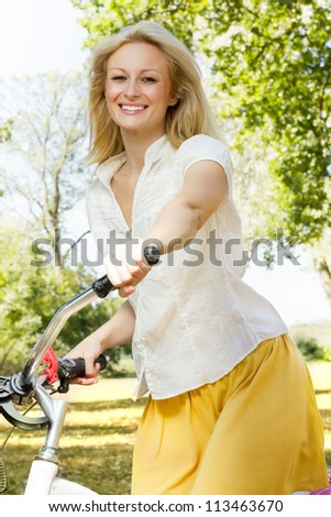 Portrait of an happy smiling young woman riding a bicycle in the park.Looking at camera. - stock photo