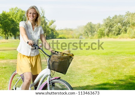 Portrait of an happy smiling young woman riding a bicycle in the park.Looking at camera.