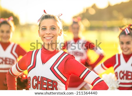Portrait of an happy young cheerleader in action outdoors - Group of girlfriends during cheerleading sport training at high school - stock photo