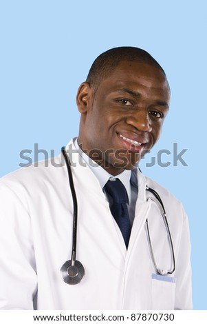 Portrait of an happy young doctor on a blue background - stock photo