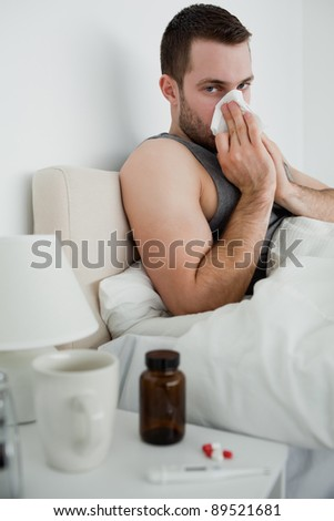 Portrait of an ill man blowing his nose in his bedroom - stock photo