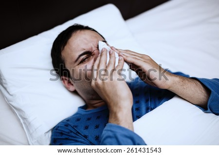 Portrait of an ill man blowing his nose in the bed