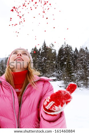 Portrait of an imaginative, young and beautiful woman in the snow mountains landscape throwing hearts shaped glitter up in the sky during a cold Christmas winter day outdoors in nature. - stock photo