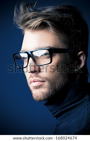 Portrait of an imposing man in elegant black clothes and glasses posing over dark background. - stock photo