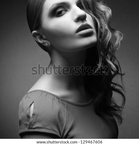 Portrait of an inaccessible beautiful ginger girl in orange dress with smoky eyes and diamond earring. Femme fatale in film noir. Hollywood style. Black and white studio shot