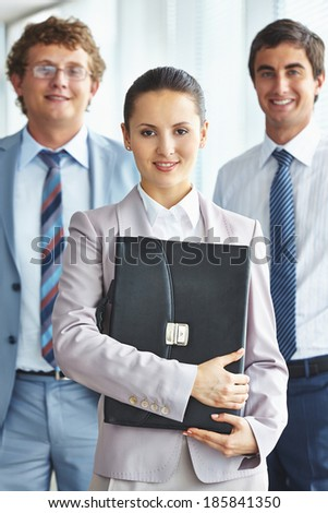 Portrait of an independent businesswoman with her colleagues on background - stock photo