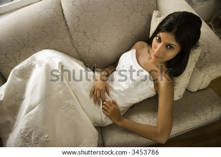 Portrait of an Indian bride lying on love seat.