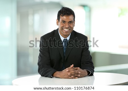 Portrait of an Indian business man sitting at a table. - stock photo
