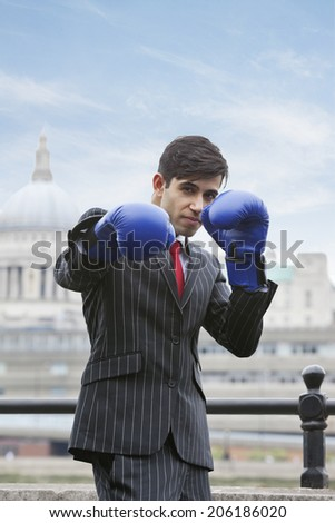 Portrait of an Indian businessman wearing blue boxing gloves with St. Paul's Cathedral in the background - stock photo