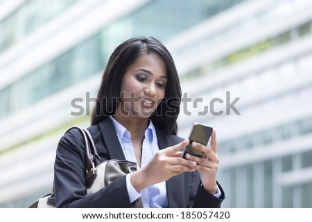 Portrait of an Indian businesswoman standing outside using mobile phone to send a message - stock photo