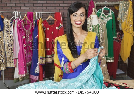 Portrait of an Indian female dressmaker working at design studio