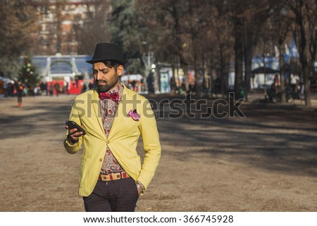 Portrait of an Indian young handsome man texting in an urban context