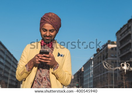 Portrait of an Indian young handsome man texting in an urban context - stock photo