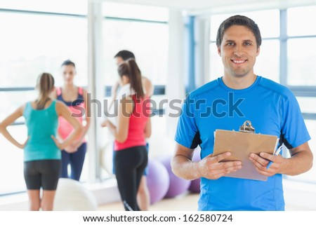 Portrait of an instructor with fitness class in background in fitness studio - stock photo