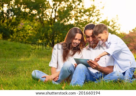 Portrait of an international family playing tablet PC in in the park. - stock photo