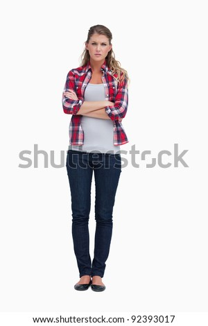 Portrait of an irritated woman with the arms crossed against a white background - stock photo