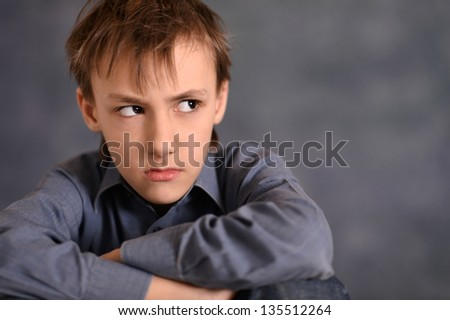 portrait of an offense little boy over a gray background - stock photo