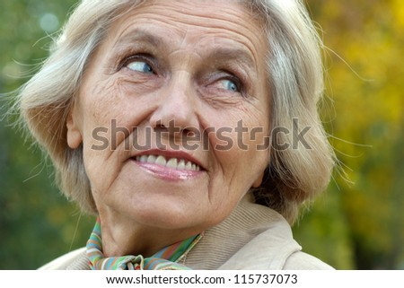 Portrait of an old beautiful woman in autumn outdoors