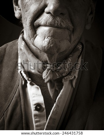 Portrait of an old cowboy in sepia, cropped portrait. - stock photo