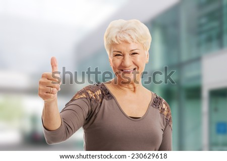 Portrait of an old lady showing OK - stock photo