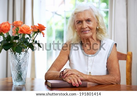 Portrait of an old lady sitting by her dining room table with book - stock photo