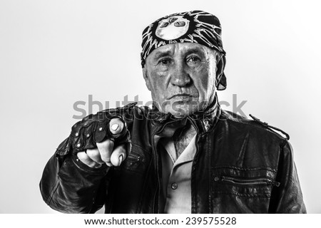 Portrait of an old man biker pointing a finger at you - stock photo