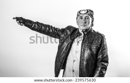 Portrait of an old man biker pointing finger - stock photo