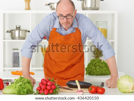 Portrait of an old man in an apron preparing to cut vegetables on a work surface in a kitchen. - stock photo