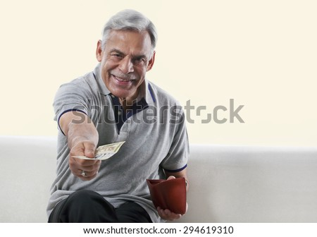 Portrait of an old man offering money - stock photo