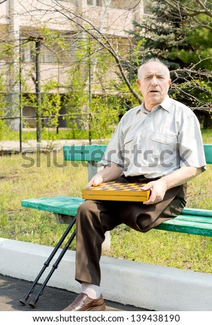 Portrait of an old man sitting on the bench park and holding chess board - stock photo