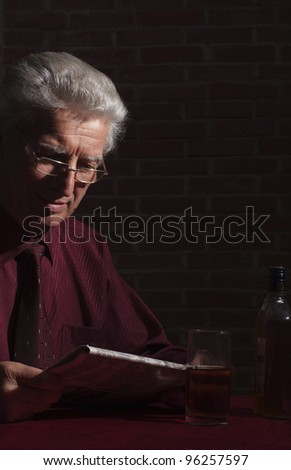 portrait of an old man with newspaper in dark