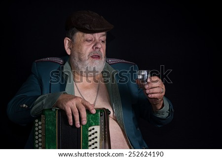 Portrait of an old retired military man who is ready to drink glass of vodka earned while playing accordion - stock photo