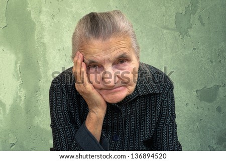 Portrait of an old woman on a vintage background. Dreaming the past. - stock photo