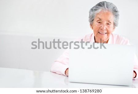 Portrait of an old woman using a computer - stock photo