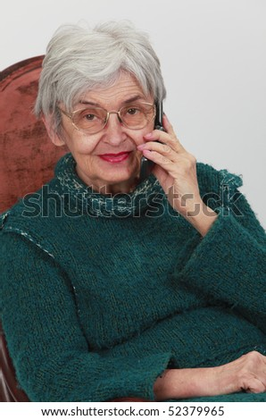Portrait of an old woman using a mobile phone.