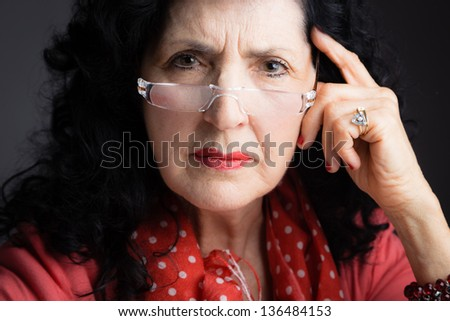 Portrait of an Old Woman Wearing Reading Glasses Looking Directly to the Camera