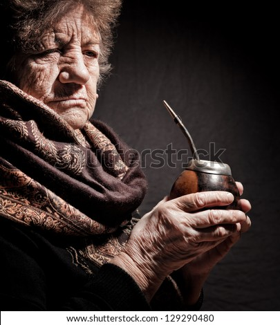 portrait of an old woman with Argentinean calabash in hands - stock photo