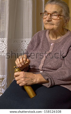 Portrait of an old woman with grinder in hands. Dreaming the past. - stock photo