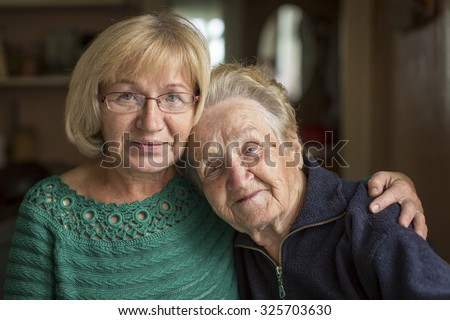 Portrait of an old woman with her adult daughter. - stock photo