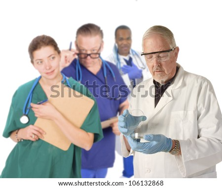 Portrait of an older doctor holding a petri dish, standing in front of his team - stock photo