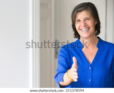 Portrait of an older woman offering a handshake - stock photo