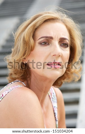 Portrait of an older woman standing alone outdoors - stock photo