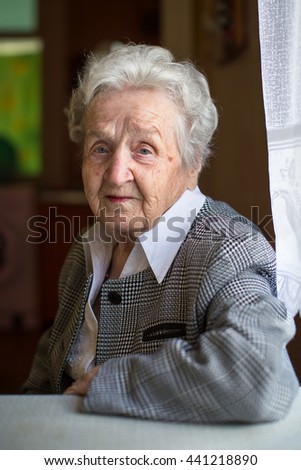 Portrait of an pensioner woman in the house. - stock photo
