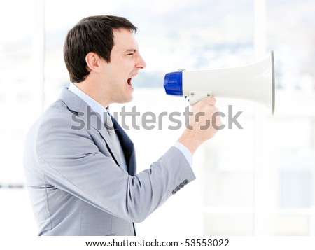 Portrait of an pretty businessman using a megaphone in the office